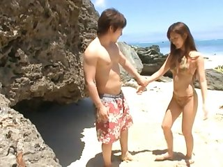 Japanese wife Rio Fujisaki drops on a catch brush knees to suck a dick by a catch sea